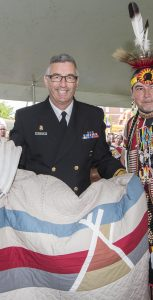 Rear-Admiral JohnNewton and members of Maritime Forces Atlantic celebrate National Aboriginal Day and enjoy Indigenous performers during the Mi'Kmaw Native Friendship Center's Mawita'Jik Let us Gather event on the Halifax Commons June 21, 2017   Halifax Mi'Kmaw Native Friendship Center and Chief Petty Officer 2nd class (Retired) Deby Eisan acknowledge RAdm Newton's support with a special presentation during National Aboriginal Day. Rear-Admiral Newton displays blanket with dancers Denise & Bert Breath Mitchell.   Photo Credit: Mona Ghiz HS88-2017-0181-228