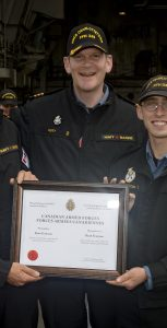 LCdr Nathan Decicco (left), XO of HMCS Charlottetown, and Cdr Jeff Hutt, CO of Charlottetown, present AB Francom with a Physical Fitness Award at sea en route to Wilhelmshaven, Germany. Photo: Cpl  J. W. S Houck, FIS Halifax