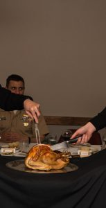 LS Collins (Left)  and Acting LCdr Dyble carve the turkey for the Trinity Detachment NOPFWI Christmas lunch. Cdr Burns CO of NOPFWI in the background. Photo: LS Steven Epple, NOPFWI