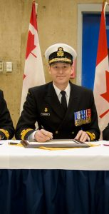 From left, Cdr Mike Eelhart, Cmdre Craig Skjerpen, and Cdr Chris Sherban sign the documents officially marking the change of command of HMCS Montreal from outgoing CO Cdr Sherban to incoming CO Cdr Eelhart. Photo: LS Dan Bard, FIS Halifax