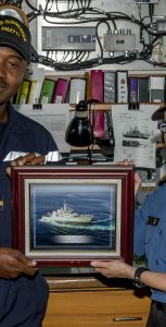 SLt Lassina Traoré, exchange officer from the Navy of Cote D'Ivoire, receives a framed photo of HMCS Summerside from LCdr Emily Lambert, CO of Summerside, during OP PROJECTION West Africa, Atlantic Ocean.  Photo: OS JOHN IGLESIAS, FIS