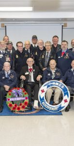 Surviving members of HMCS Kootenay, who were on board during the gearbox explosion in 1969, pose for a photo at the ceremony marking 49 years since the incident. Many are wearing the newly created HMCS Kootenay ribbon. LS BRAD UPSHALL, 12 WING IMAGING