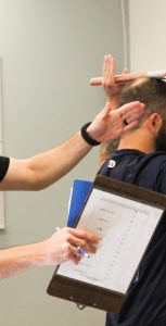 PSP fitness and sports instructor Mike Dodge (left) examines his client's range of motion as part of the reconditioning program. RYAN MELANSON, TRIDENT STAFF