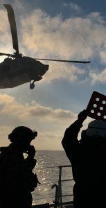 A crewmember onboard HMCS Yellowknife and members of a US Coast Guard Maritime Security Response Team await the arrival of a US Navy MH-60 helicopter for a training exercise during Op CARIBBE, in the Pacific Ocean on March 25, 2019. CAPT ANNIE MORIN
